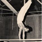 Barry Weinstein on the parallel bars with Ken Matzick spotting in 1959
